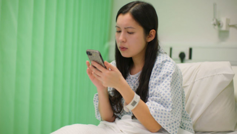 Concerned-Hospital-Patient-Sits-Up-Using-Phone