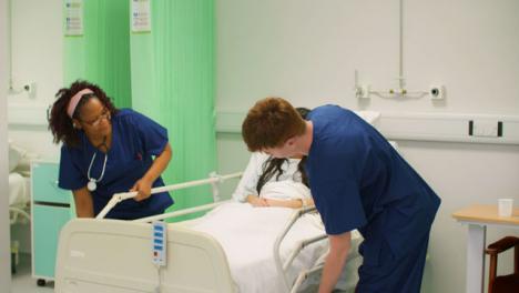 Dos-enfermeras-bajan-los-rieles-de-la-cama-del-hospital