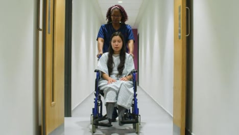 Nurse-Pushes-Patient-In-Wheelchair-in-Corridor