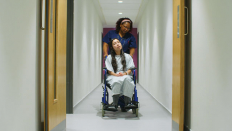 Nurse-Pushes-Patient-In-Wheelchair-Down-Corridor