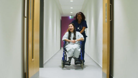 Female-Nurse-Pushes-Happy-Patient-In-Wheelchair