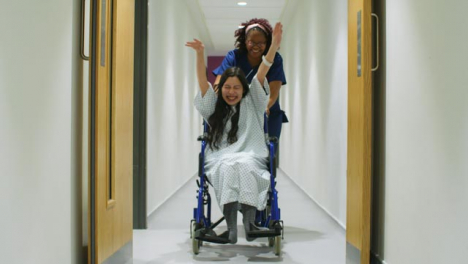 Female-Nurse-Having-Fun-With-Patient-In-Wheelchair