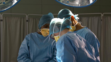 Surgeons-Standing-Looking-Down-At-Surgery