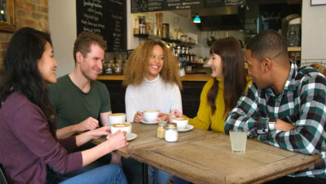 A-group-of-friends-socialising-around-table-in-cafe