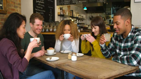 A-Group-Of-Friends-Chatting-And-Drinking-Coffee-At-Table-In-Cafe