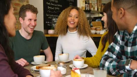 Pan-de-amigos-socializando-alrededor-de-la-mesa-en-el-café