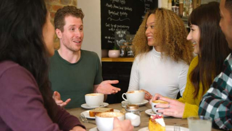 Pan-Of-Friends-Chatting-And-Laughing-Around-Table-In-Cafe