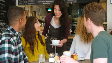 Friends-Socialising-In-Cafe-Being-Served-By-Waitress