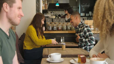 Two-Couples-Talking-And-Laughing-At-Tables-In-Cafe