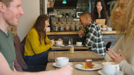 Two-Couples-Talking-At-Tables-In-Cafe