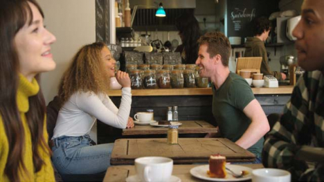 Male-Friend-Arrives-At-Cafe-And-Greets-Friend-At-Table