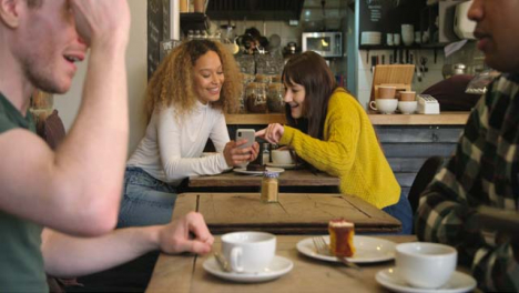 Two-Women-Talking-At-Table-In-Cafe