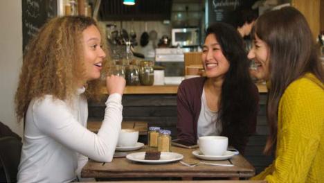 Gruppe-Von-Freundinnen-Die-Am-Tisch-Im-Café-Lachen-Und-Plaudern