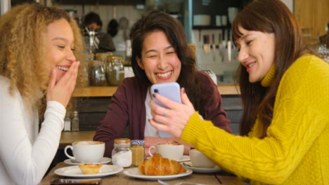 Pan-of-Woman-Showing-Her-Friends-Something-Funny-On-Phone-In-Cafe