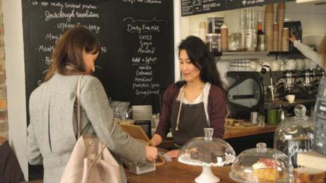 Weibliche-Kunden-Die-Sich-An-Der-Theke-Im-Café-Anstellen-und-Bezahlen-