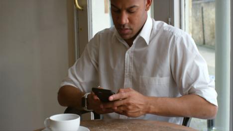 Tilt-Up-Male-customer-sitting-in-cafe-using-smartphone