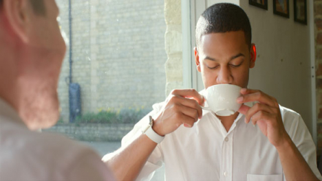 Close-up-two-men-sitting-in-cafe-talking-and-drinking