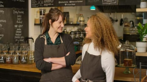 Two-happy-female-baristas-at-a-cafe-smiling-at-each-other