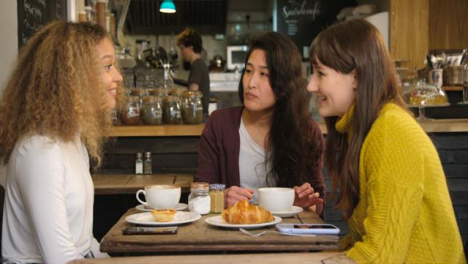 Group-Of-Female-Friends-Chatting-And-Laughing-At-Table-In-Cafe