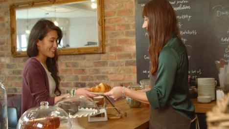 El-dueño-del-café-pasa-el-croissant-al-cliente