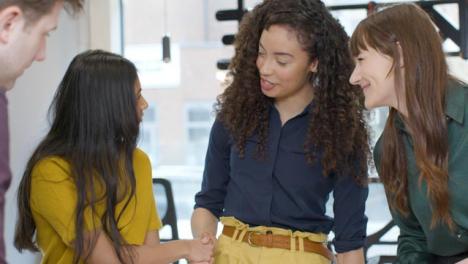 Colegas-trabajando-juntos-dándose-la-mano-en-una-reunión
