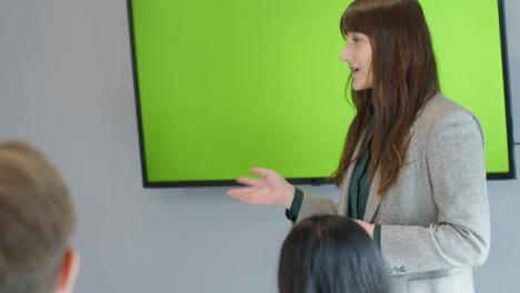 Geschäftsfrau-Präsentiert-Kollegen-Mit-Greenscreen-TV