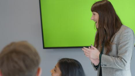 Feliz-empresaria-dando-presentación-a-colegas-con-pantalla-verde-tv
