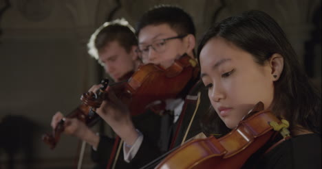 Pull-Focus-Three-Violinists-Playing-Together-