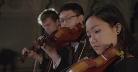 Pull-Enfoque-Tres-violinistas-tocando-juntos