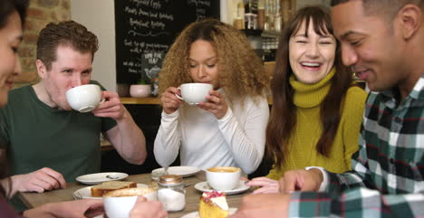 Panning-Across-Group-Of-Friends-Chatting-And-Drinking-Coffee-In-Cafe