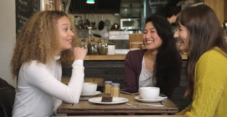 Group-Of-Female-Friends-Laughing-And-Chatting-At-Table-In-Cafe