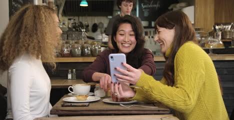 Una-Mujer-Muestra-A-Sus-Amigos-Algo-Divertido-Por-Teléfono-En-La-Cafetería-