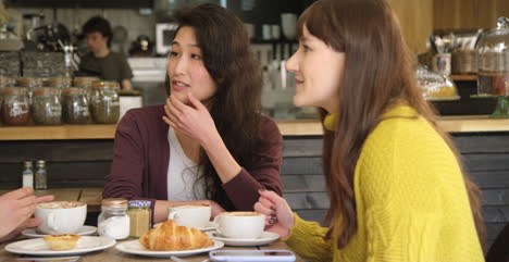 Panning-Across-three-friends-chatting-at-table-in-cafe
