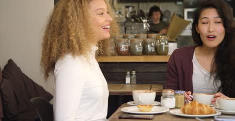 Paneo-a-través-de-tres-amigos-socializando-alrededor-de-la-mesa-en-el-café