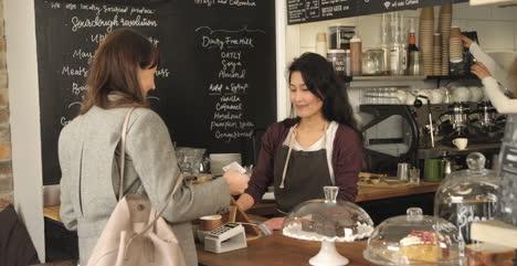 Clienta-Haciendo-Cola-Y-Haciendo-El-Pago-En-El-Mostrador-Del-Café