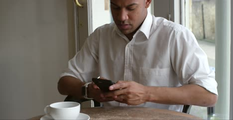 Tilt-Up-Male-customer-sitting-in-cafe-using-smartphone