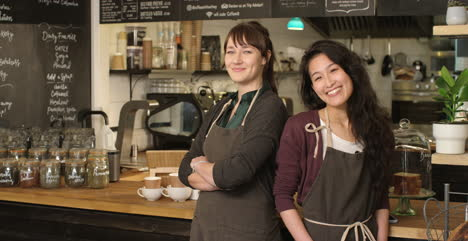 Portrait-of-two-happy-female-baristas-at-cafe-smiling-to-camera