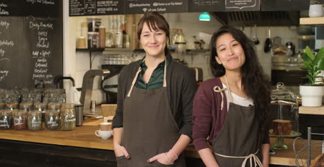 Portrait-of-two-female-baristas-at-a-cafe-smiling-to-camera