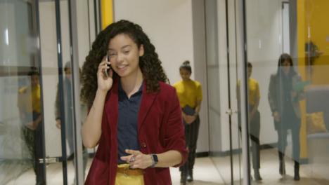Businesswoman-Talking-On-Smartphone-In-Corridor