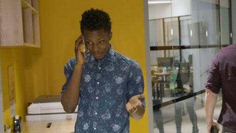 Man-Talking-On-Smartphone-In-Corridor