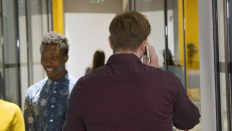 Rear-View-Businessman-Talking-On-Smartphone-In-Corridor