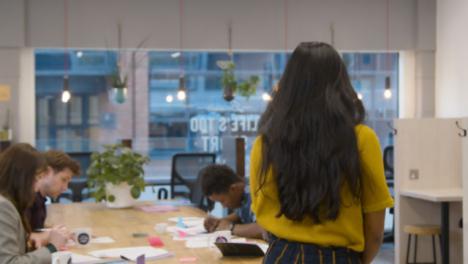 Mujer-caminando-en-una-oficina-y-sentado-con-colegas