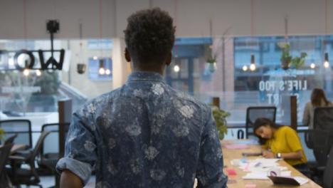 Hombre-caminando-en-una-oficina-y-sentado-con-colegas