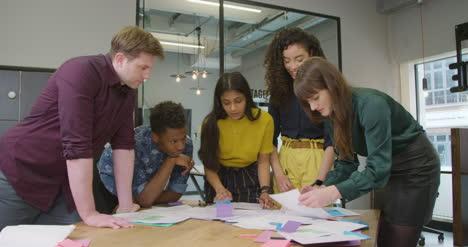 Pan-De-Empresaria-En-Discusión-Con-Colegas-En-El-Espacio-De-La-Oficina-Moderna