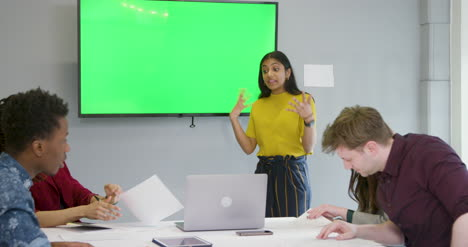 Woman-Leading-Meeting-Colleagues-With-Green-Screen-Tv