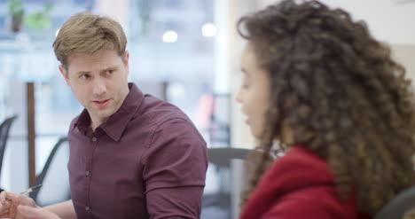 Hombre-Y-Mujer-Hablan-Y-Trabajan-Juntos-En-La-Oficina