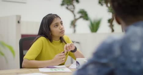 Mujer-Hablando-Con-Colegas-En-El-Espacio-De-La-Oficina-Moderna