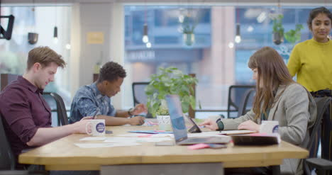 Woman-hands-notes-to-colleague-in-open-plan-office