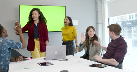 Happy-Colleagues-With-Green-Screen-Tv-Clapping-And-High-Fiving