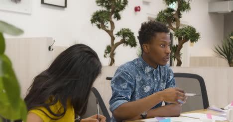 Hombre-hablando-con-colegas-en-la-oficina-de-plan-abierto
